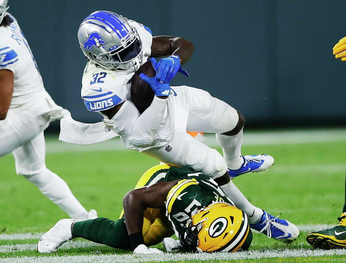 GREEN BAY, WISCONSIN - SEPTEMBER 20: D'Andre Swift #32 of the Detroit Lions is tackled by Darnell Savage #26 of the Green Bay Packers during the first half at Lambeau Field on September 20, 2021 in Green Bay, Wisconsin. (Photo by Wesley Hitt/Getty Images)