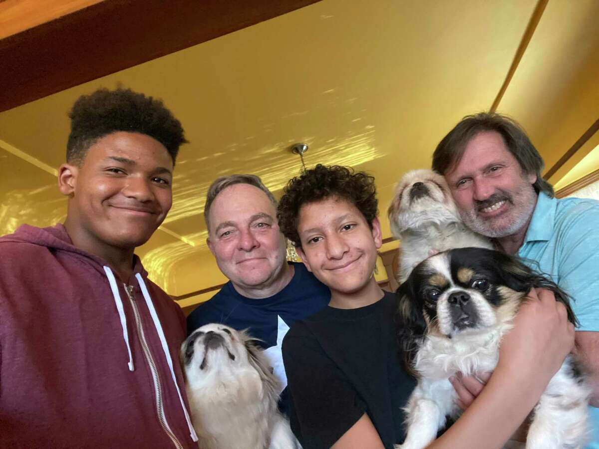The Fisher-Paulson family -- sons Zane (far left) and Aidan with parents Kevin (left) and Brian, and their dogs.