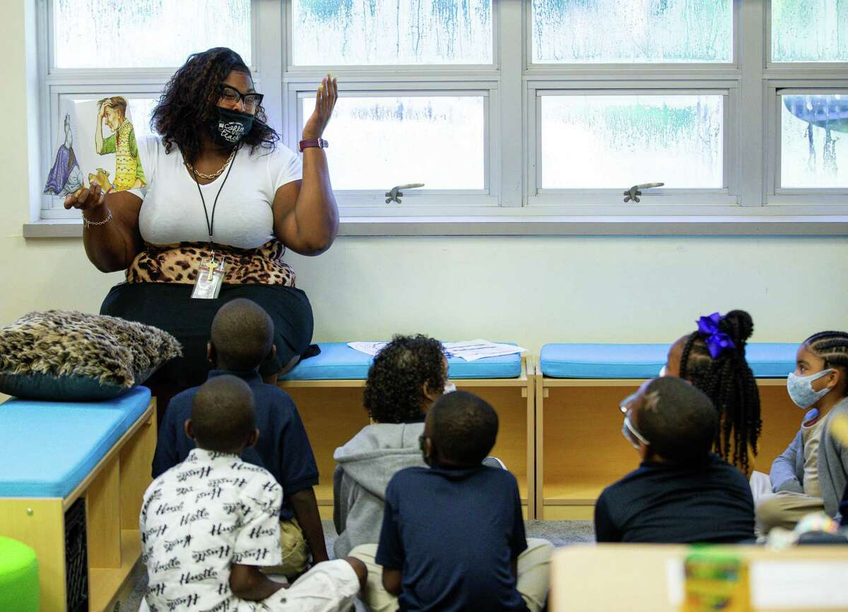Quanesha Hollins, left, who teaches second grade at Mabel B. Wesley Elementary School, reads a book to her students during the first day of school on Monday, Aug. 23, 2021, in Houston. HISD is currently requiring masks in all of its buildings. On Sept. 17, the Texas Education Agency said that districts can't require students and staff to wear masks due to Gov. Greg Abbott's order banning mask mandates.