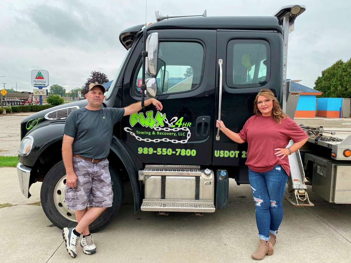 Cory and Bonnie Maxwell, owners of MAX 24HR Towing and Recovery and MAX Superior Shine in Bad Axe, pose with one of their tow trucks. (Mark Birdsall/Huron Daily Tribune)