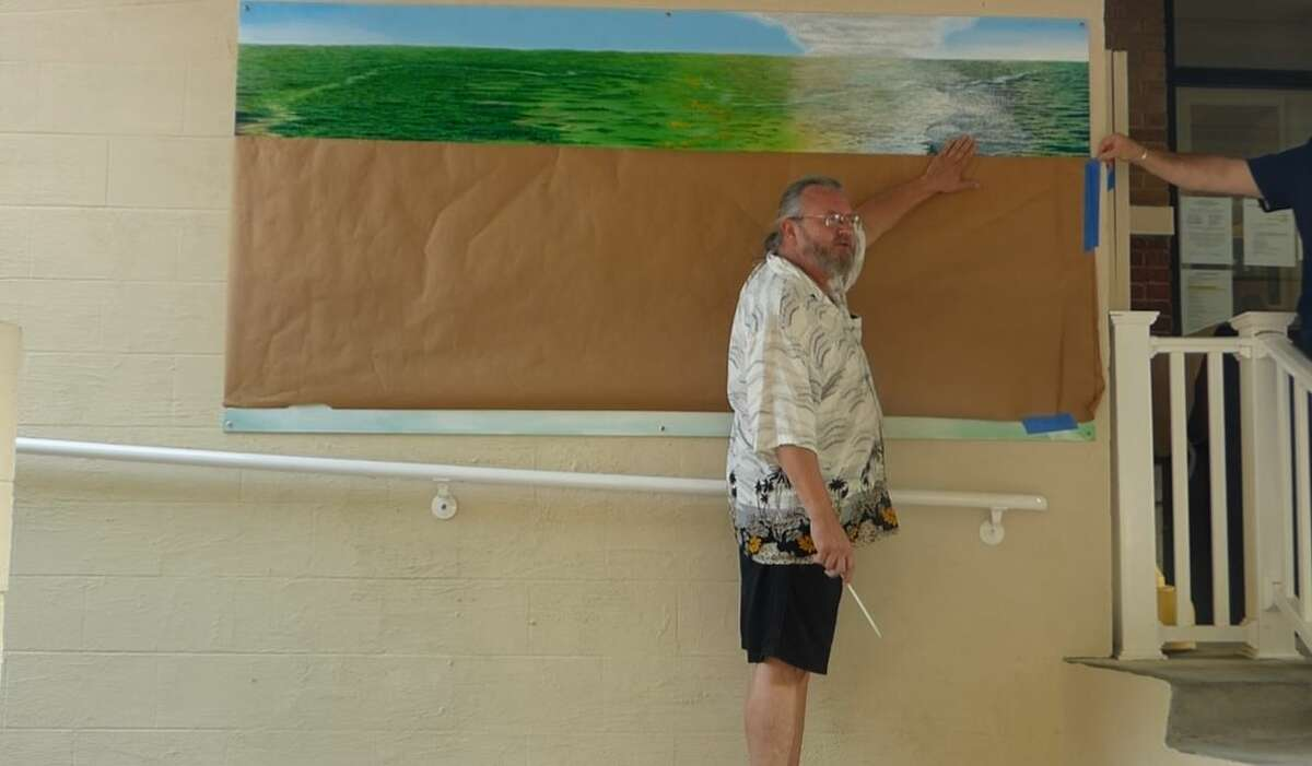 Manistee-area artist, William Hattendorf unveils a painting in recognition of Marilla Township's sesquicentennial celebration.