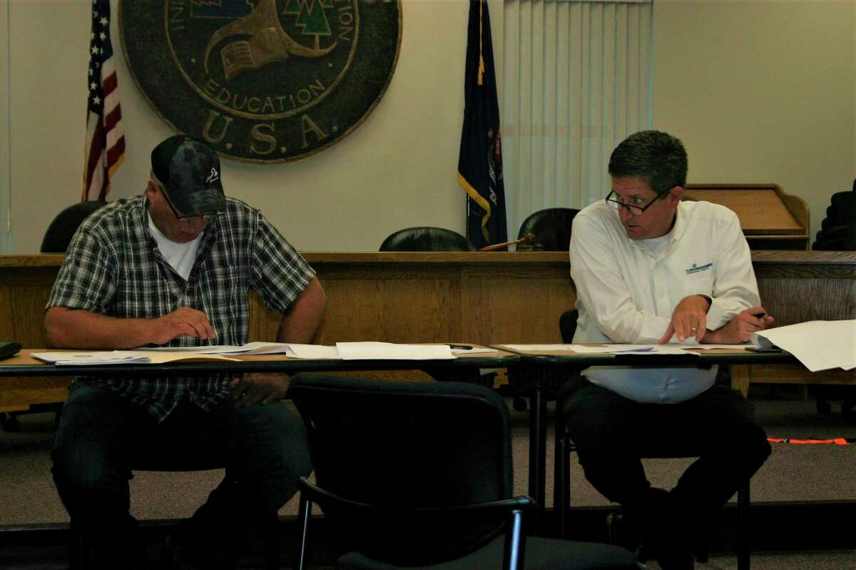 CrawfordContracting, Inc. superintendent Jamey Loomis (left) and Fleis & VandenBrik Engineering, Inc., project engineer Todd Richter (right) compare notes during the Hemlock Park preconstruction meeting last week. Utility construction at he park is set to begin later this month. (Pioneer photo/Cathie Crew)
