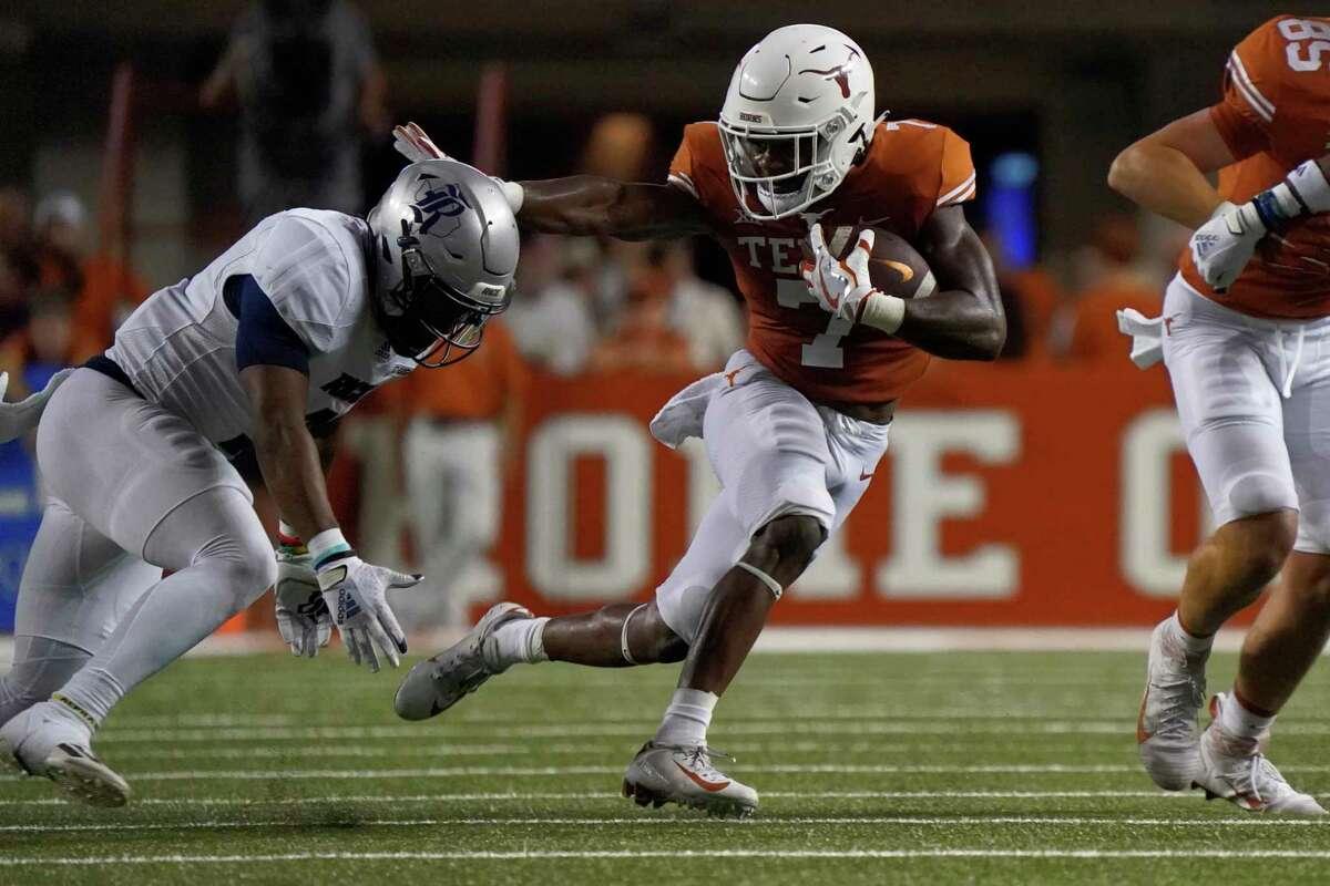 Texas running back Keilan Robinson (7) runs against Rice safety Kirk Lockhart (9) during the second half of an NCAA college football game on Saturday, Sept. 18, 2021, in Austin, Texas. (AP Photo/Chuck Burton)