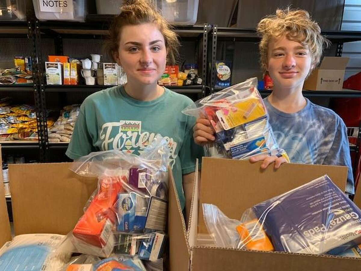 Ashley and Matthew Reel sorts donations to be distributed to those in need in the community. Ashley collected prom dresses for peers after Harvey. Matthew collects food and other supplies.
