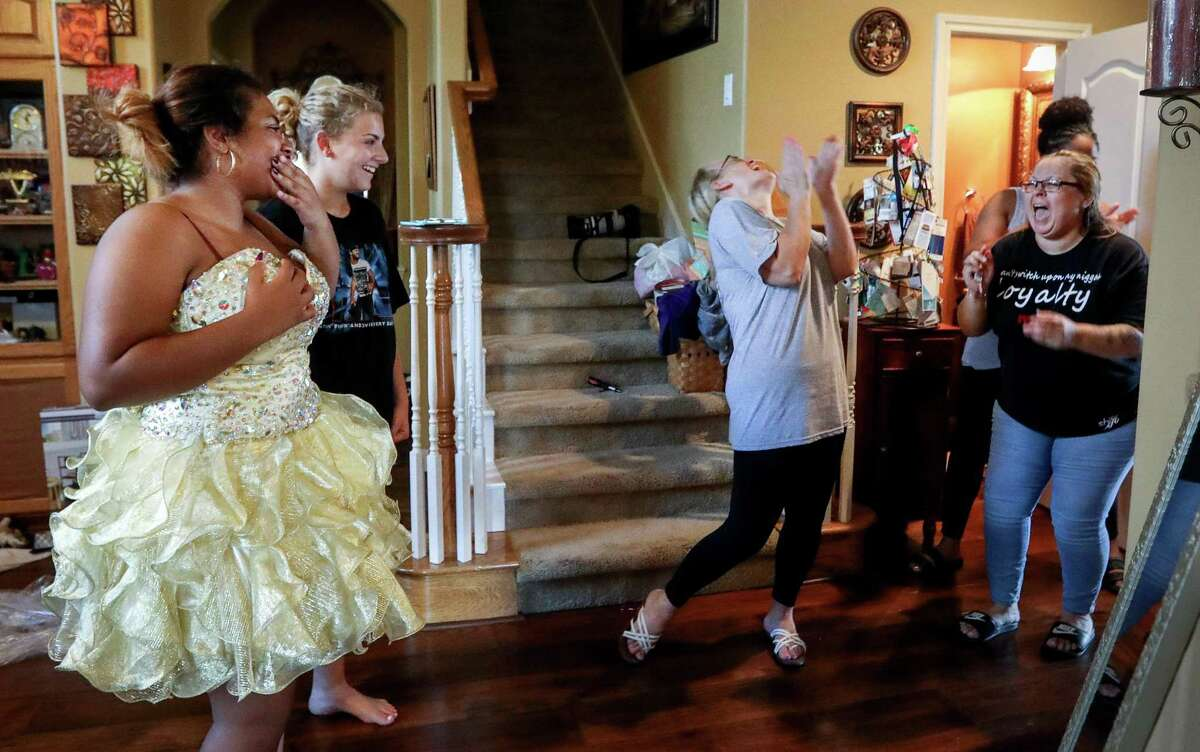 """Janiyah Tells, 16, from left, Ashley Reel, 14, her mother Tammy Reel, Ronisha Banks, face not shown, and Tells' mother Rosenda Cuevas, react after Ashley Reel asked Tells, """"Do you say yes to the dress,"""" Sunday, Sept. 24, 2017, in Spring. Ashley Reel collected homecoming dresses to distribute to victims of Hurricane Harvey in 2017. ( Jon Shapley / Houston Chronicle )"""