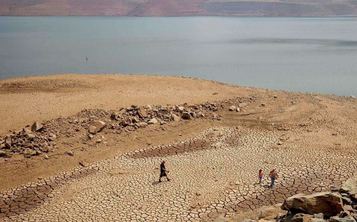 In this photograph from August, a family walks over cracked mud near Lake Oroville's shore as water levels remain low because of continuing drought conditions.