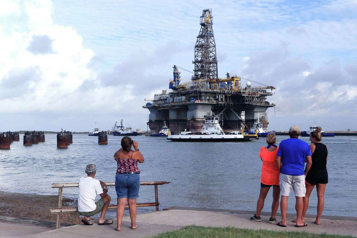 Richard Jones (from left) Dee Dee Cruz, Tane McGehee, Dennis McGehee and Mollie McGeehee watch as the Noble Jim Day, one of the world's largest offshore oil rigs, travels through the ship channel on Thursday, July 28, 2016 in Port Aransas. The rig was docked at Gulf Copper.