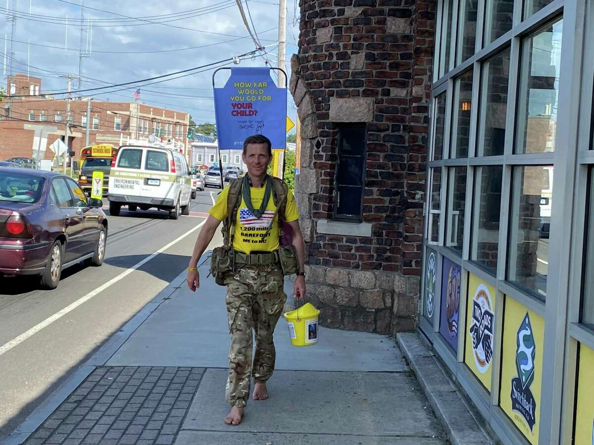 Chris Brannigan walks through Milford on Day 21 of his 1,200-mile barefoot solo walk from Maine to North Carolina to raise funds to develop a gene therapy for a genetic disorder that affects his daughter.