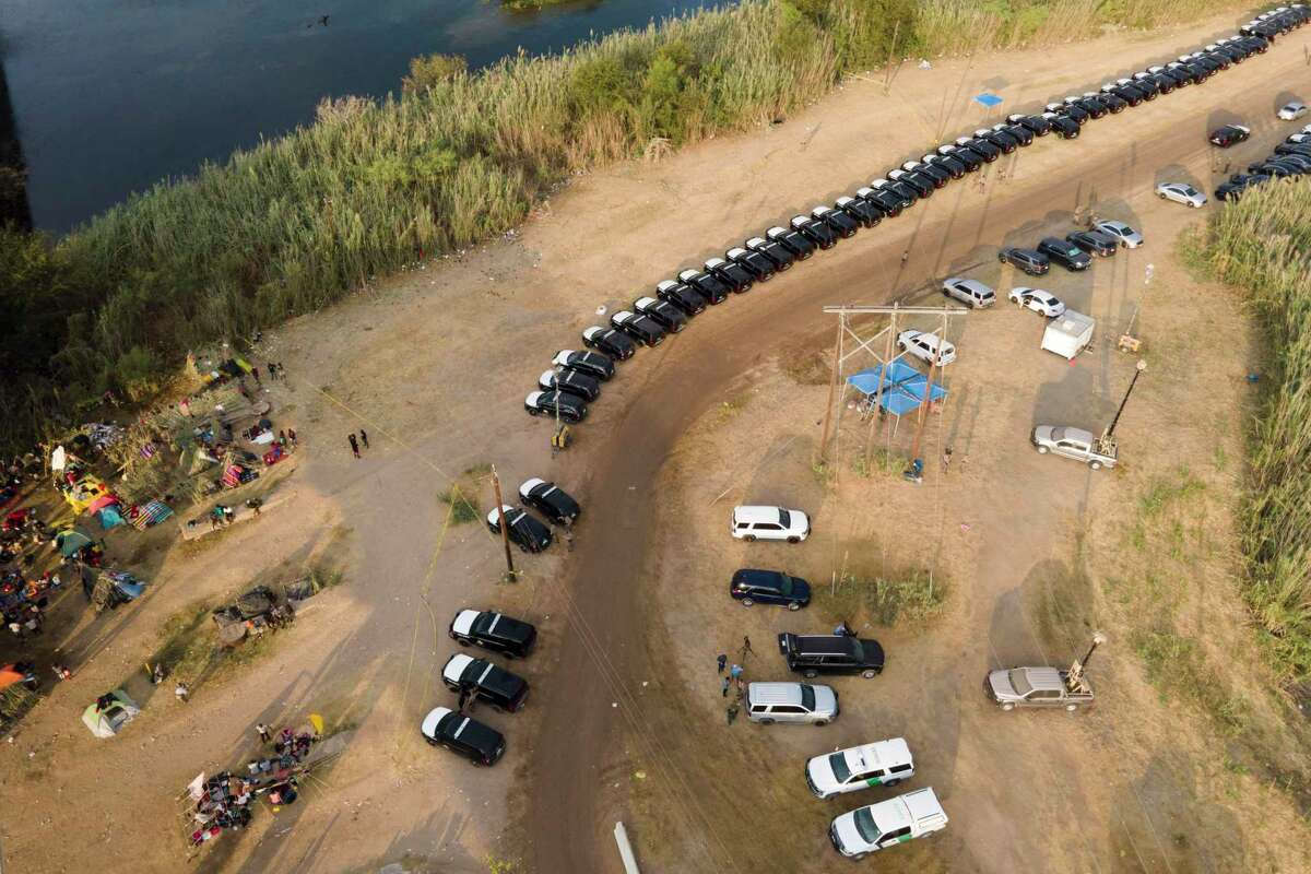 Texas Department of Safety vehicles line up along the bank of the Rio Grande near an encampment of migrants, many from Haiti, near the Del Rio International Bridge, Tuesday, Sept. 21, 2021, in Del Rio, Texas. The U.S. is flying Haitians camped in a Texas border town back to their homeland and blocking others from crossing the border from Mexico. (AP Photo/Julio Cortez)