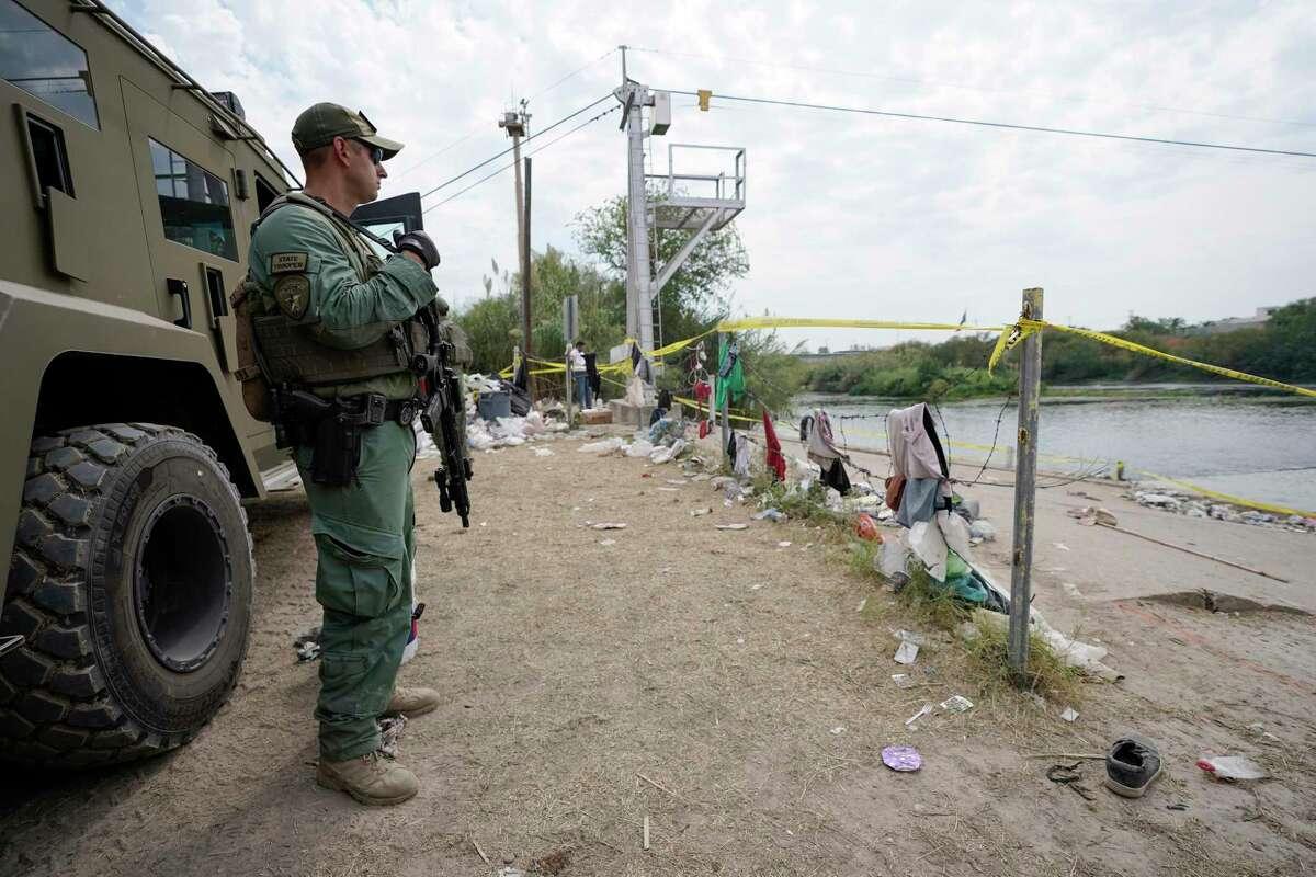 A Texas Department of Safety official stands near an armor vehicle along the Rio Grande, Tuesday, Sept. 21, 2021, in Del Rio, Texas.