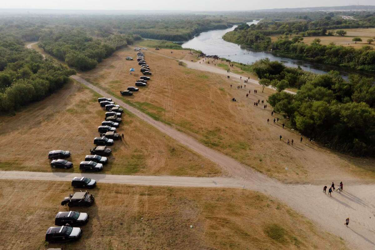 Official vehicles line up along the bank of the Rio Grande near an encampment of migrants, many from Haiti, near the Del Rio International Bridge, Tuesday, Sept. 21, 2021, in Del Rio, Texas. The U.S. is flying Haitians camped in a Texas border town back to their homeland and blocking others from crossing the border from Mexico. (AP Photo/Julio Cortez)