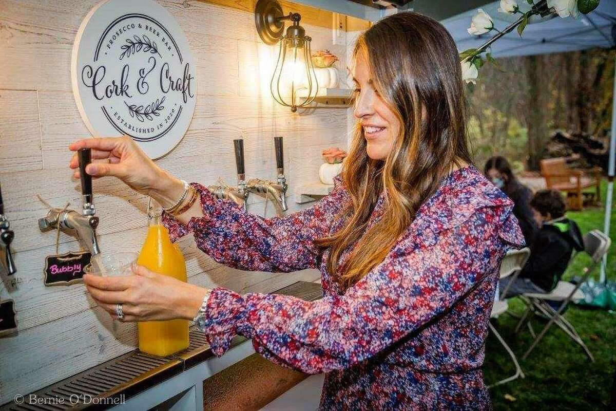 Tara Capelli of Branford pours a drink at her Cork & Craft mobile prosecco and craft beer bar.