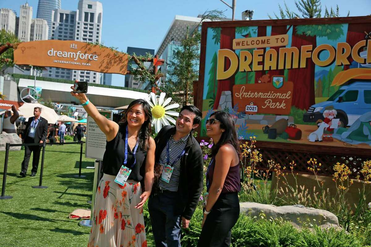 Salesforce's staff Taksina Eammano (l to r), Victor Liu and Nithya Lakshmanan take a photo at the entrance to the International Park while attending Salesforce's Dreamforce 2021 conference at Moscone Center in San Francisco.