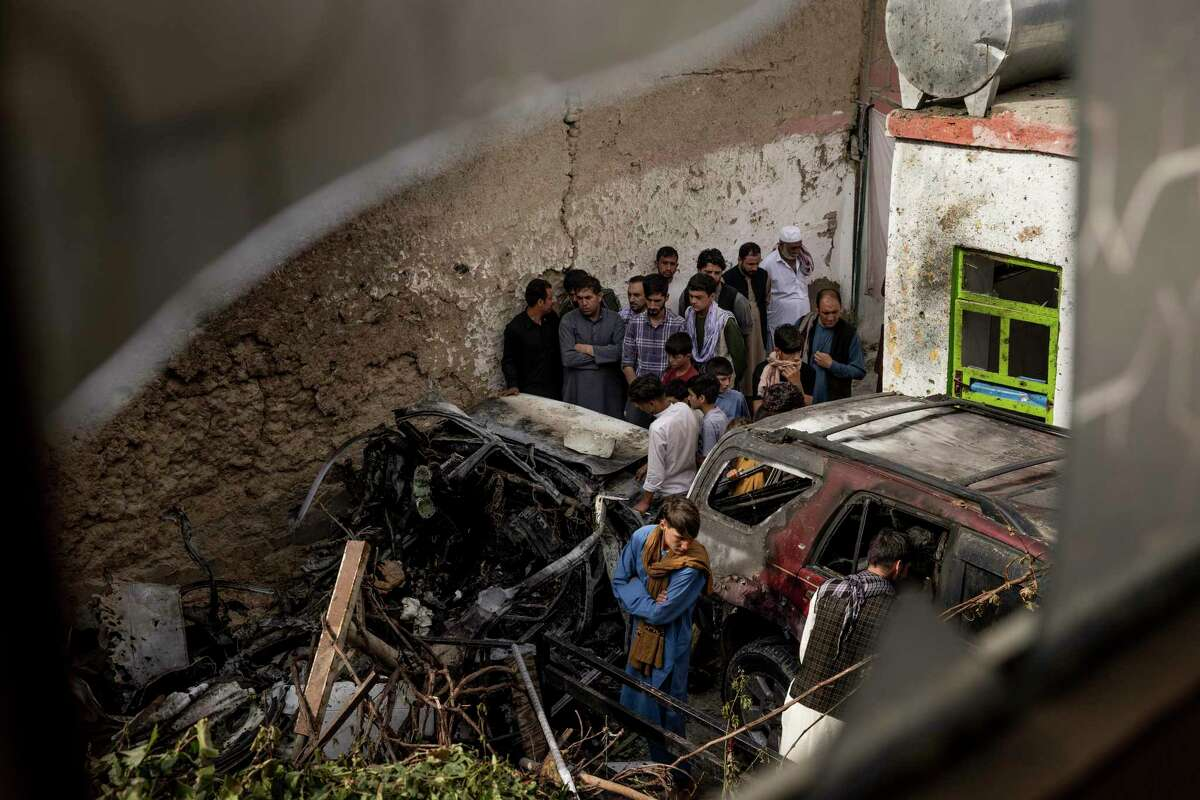 Relatives and neighbors gather near damage from a U.S. drone strike in the courtyard of Zemari Ahmadi's home in Kabul, Afghanistan, Aug. 30, 2021. The Pentagon continued to assert on Monday, Sept. 13, that the last U.S. drone strike in Afghanistan was necessary to prevent an attack on American troops, despite a New York Times investigation that raised doubts about the military's version of events, including whether explosives were in the vehicle that was blown up and whether the driver had a connection to the Islamic State. (Jim Huylebroek/The New York Times)