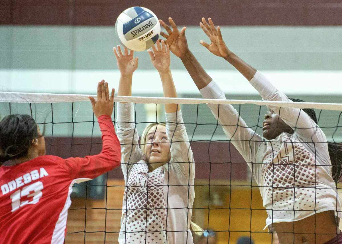 Legacy High's Callie McCright and Loredana Fouonji go up for the block as Odessa High's Clarissa Rodriguez hits it 09/21/2021 at Legacy High School gym. Tim Fischer/Reporter-Telegram
