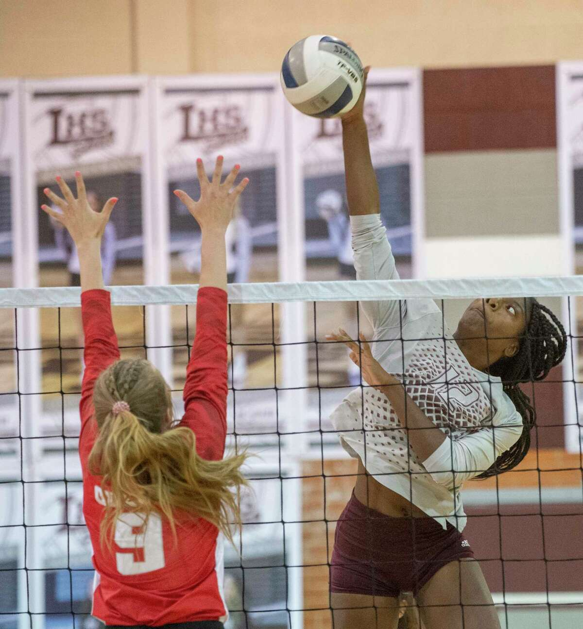 Legacy High's Christallyn Tate goes up high for the kill shot as Odessa High's Paige Byford tries to block 09/21/2021 at Legacy High School gym. Tim Fischer/Reporter-Telegram