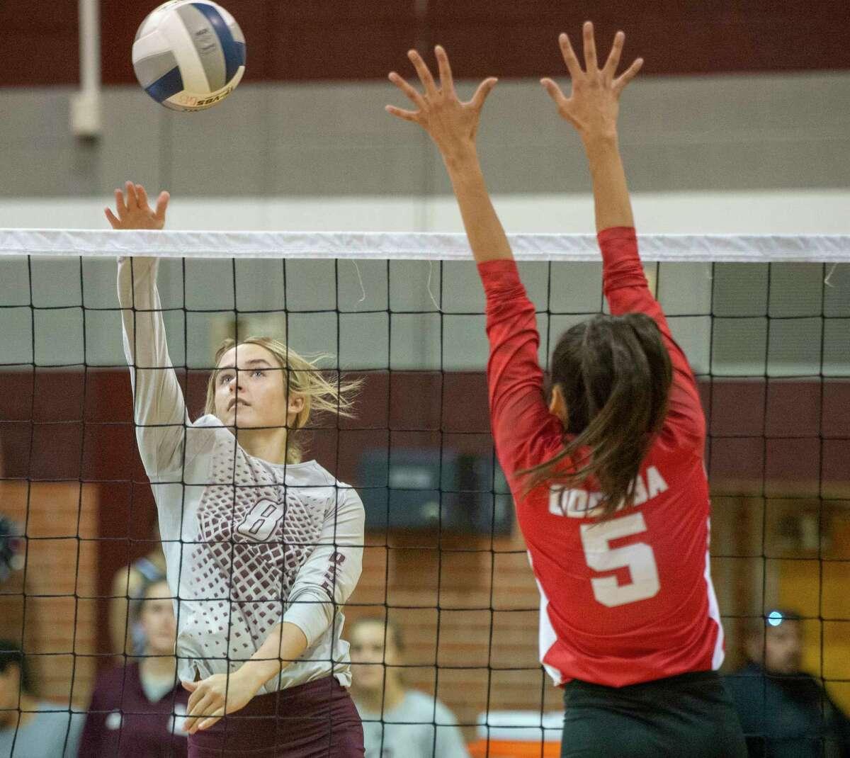 Legacy High's Callie McCright tips the ball out of reach of Odessa High's Aubrey Villa 09/21/2021 at Legacy High School gym. Tim Fischer/Reporter-Telegram