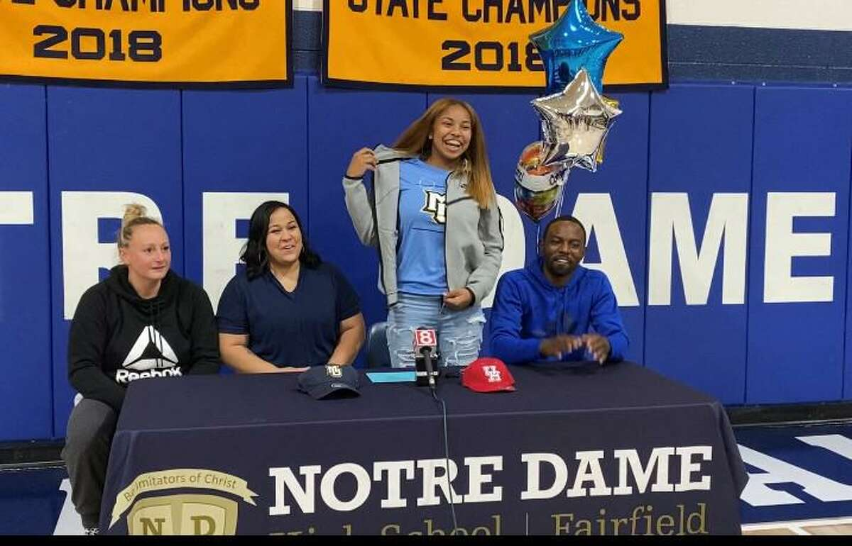 Aizhanique Mayo of Notre Dame-Fairfield reveals her t-shirt as she announces her intention to attend Marquette University to play women's basketball on Tuesday, Sept. 21, 2021 in Fairfield, Conn. Sitting with her are her parents and Notre Dame coach Maria Conlon.