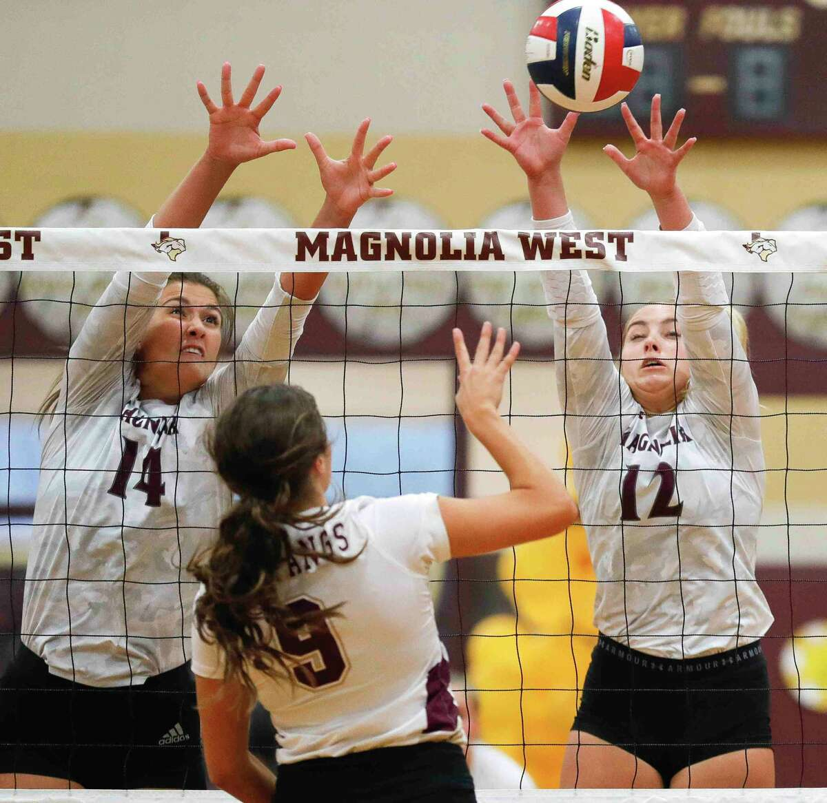 Magnolia's Sydney Gentry (12) block a shot by Magnolia West's Addison Roden beside Magnolia's Alex Bull (14) during the first set of a District 19-5A high school volleyball match at Magnolia West High School, Tuesday, Sept. 21, 2021, in Magnolia.