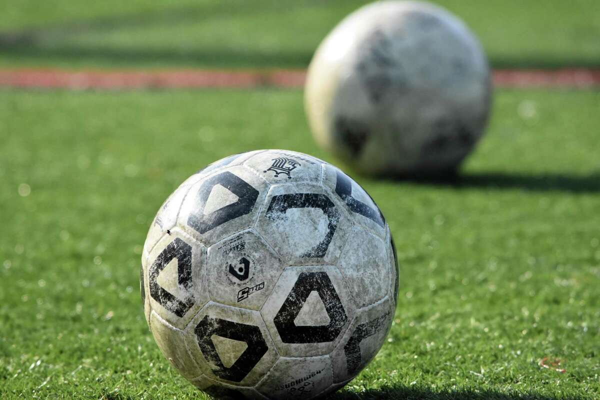 Soccer balls lay on the field during a practice.