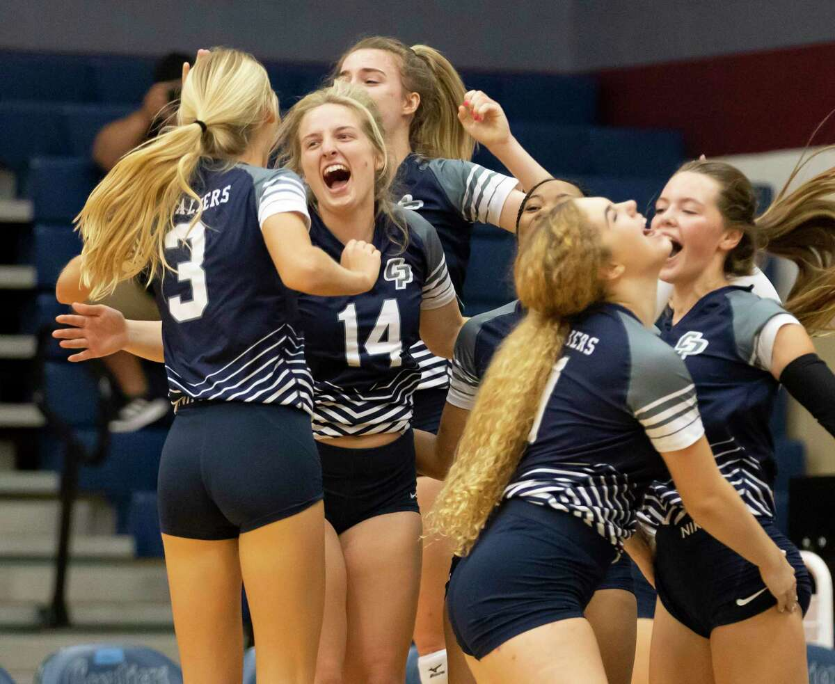 College Park volleyball players react after they win the second set of a District 13-6A volleyball match against Grand Oaks at College Park High School, Tuesday, Sept. 21, 2021, in The Woodlands.