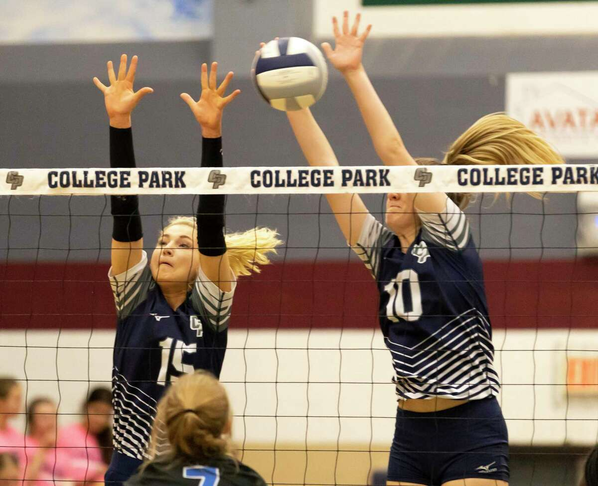 College Park setter Paige Bernstein (15) and middle hitter Cassidy Coperland (10) block the ball from Grand Oaks during the first set of a District 13-6A volleyball match at College Park High School, Tuesday, Sept. 21, 2021, in The Woodlands.