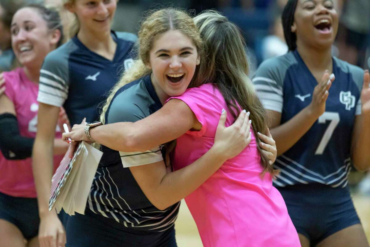 College Park setter Molly Harris (11) is embraced by her head coach Candice Gibson after they win third set of a District 13-6A volleyball match against Grand Oaks at College Park High School, Tuesday, Sept. 21, 2021, in The Woodlands.