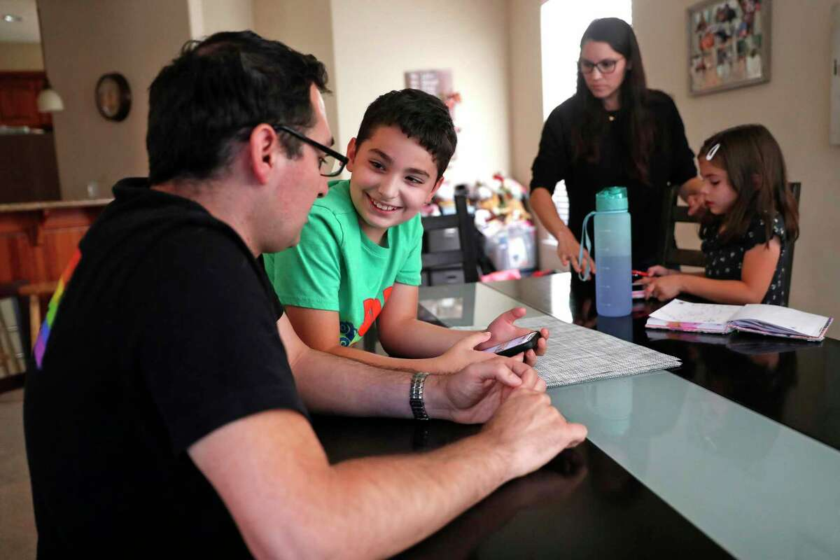 Miguel Chavez and his son, Nico, 9, order dinner on an app as his wife, Renee, interacts with their daughter, Sofia, 6, at their home in Castro Valley, Calif., on Monday, September 20th, 2021. The Chavez children were enrolled in a COVID-19 vaccine trial at Stanford.