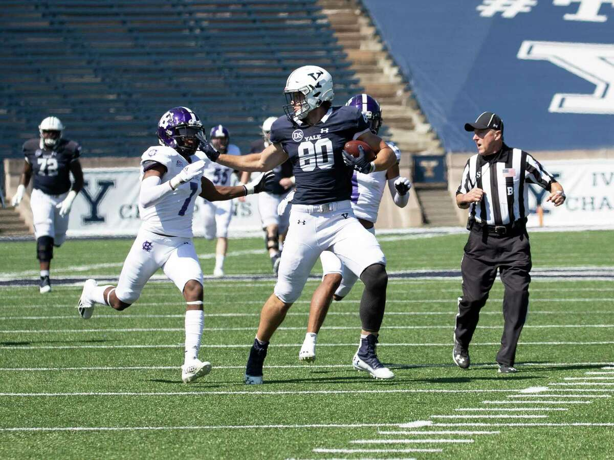 Yale tight end JJ Howland fends off Holy Cross defender John Smith during Saturday's game.