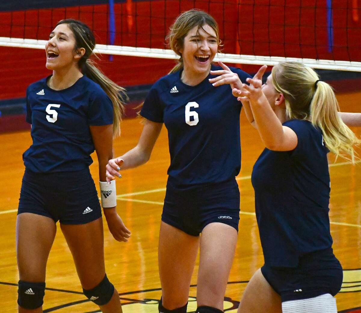 Plainview players Daniela Guzman (5), Adri Martin (6) and Haley Curtis react to a point during their non-district volleyball game against Idalou on Tuesday in the Dog House.