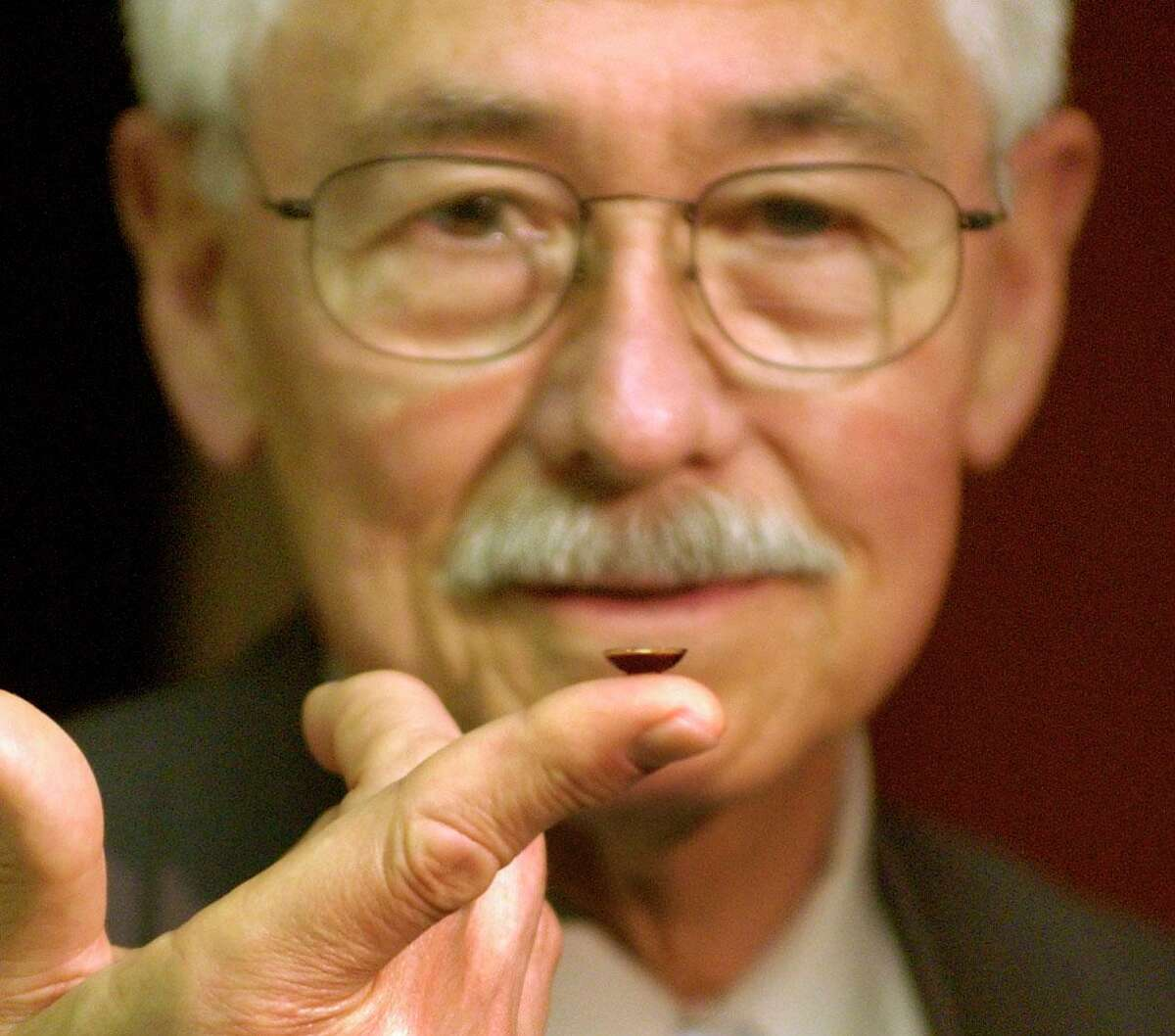 In this undated archive photo, Dr. Richard Ruiz, chairman of the Ophthalmology Department at the University of Texas Health Science Center at Houston, holds a contact lens that study participants say gives immediate relief from migraines.