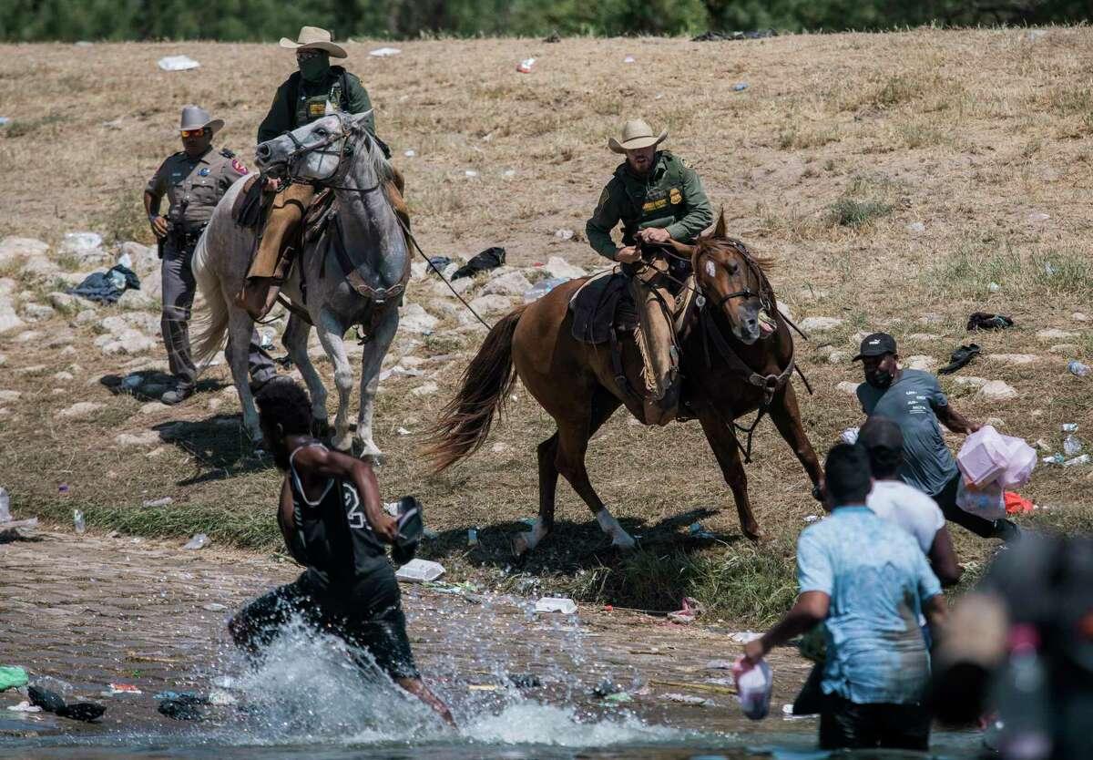 Agentes montados de Aduanas y Protección Fronteriza intentan contener a migrantes al cruzar el Río Grande desde Ciudad Acuña, México, hacia Del Río, Texas, el domingo 19 de septiembre de 2021.