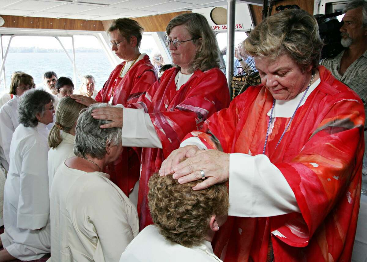 Nine women challenging the Roman Catholic Churches ban on female priests kneel in front of Bishops as a part of a unoffical ordination ceremony on a boat on the St. Lawrence River off the shores of Ganonoque, Ont. Monday, July 25, 2005. (AP Photo/CP Photo/Jonathan Hayward)