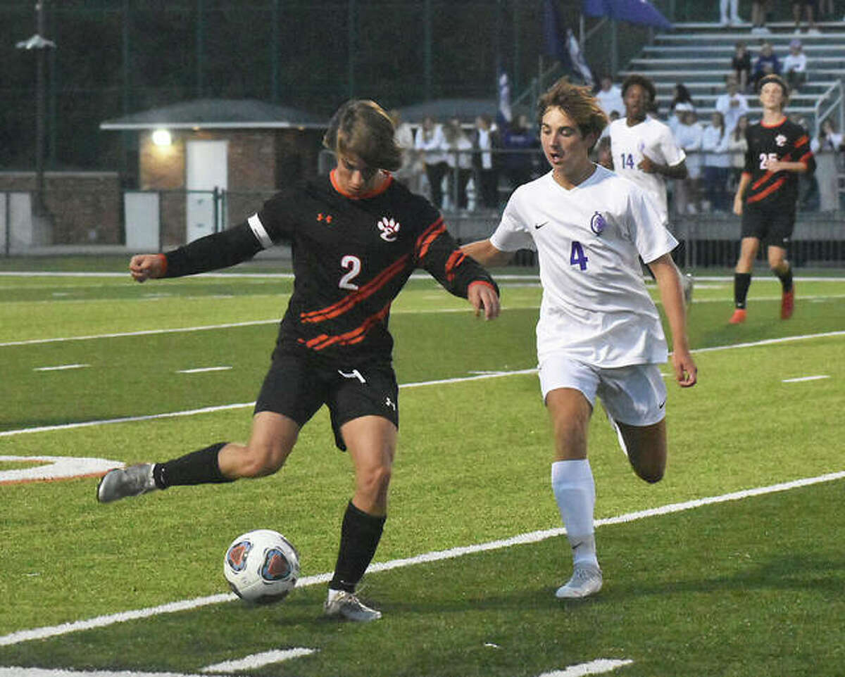 Edwardsville's Jake Duboise, left, clears the ball down the field away from Collinsville's Adam Reiniger during the first half.
