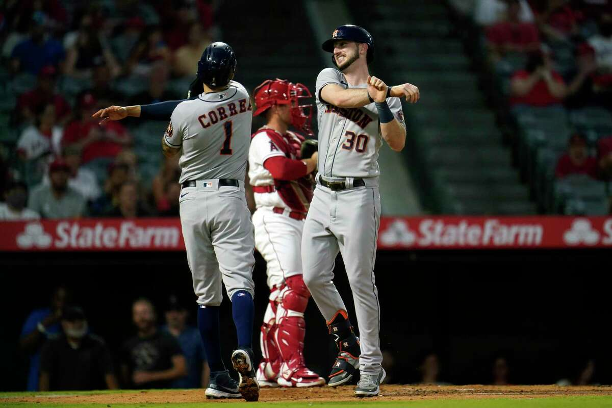 Kyle Tucker (right) celebrates his two-run home run with Astros teammate Carlos Correa during the second inning of Tuesday's 10-5 win over the Angels.