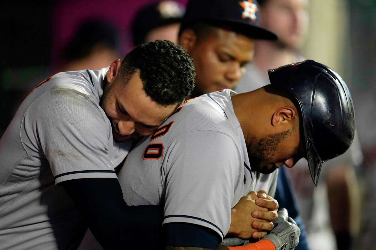 Houston Astros' Martin Maldonado, right, is hugged by Carlos Correa after Maldonado's solo home run during the sixth inning of a baseball game against the Los Angeles Angels Tuesday, Sept. 21, 2021, in Anaheim, Calif. (AP Photo/Marcio Jose Sanchez)