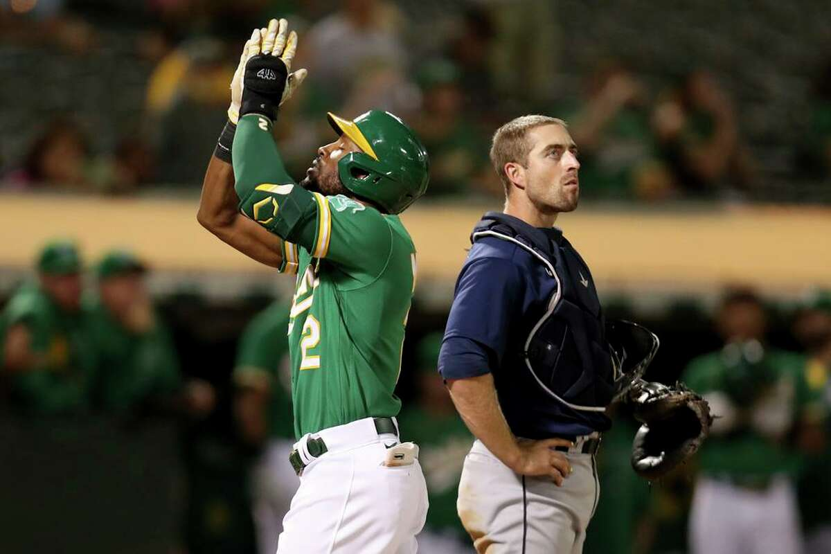 Oakland Athletics' Starling Marte, left, points to the sky after hitting a solo home run in front of Seattle Mariners' Tom Murphy, right, during the fourth inning of a baseball game in Oakland, Calif., Tuesday, Sept. 21, 2021. (AP Photo/Jed Jacobsohn)