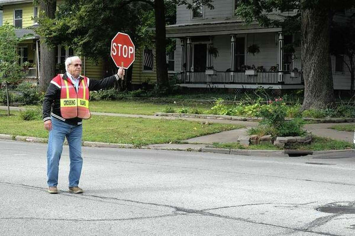 Ken Wallbaum, a crossing guard of more than 10 years, stops cars Tuesday for Washington Elementary School students to cross at West College Avenue at North Prairie Street.