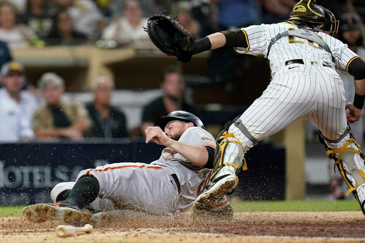 San Francisco Giants' Brandon Belt, below, scores off an RBI-single by LaMonte Wade Jr. as San Diego Padres catcher Austin Nola looks on, above, during the ninth inning of a baseball game Tuesday, Sept. 21, 2021, in San Diego. (AP Photo/Gregory Bull)