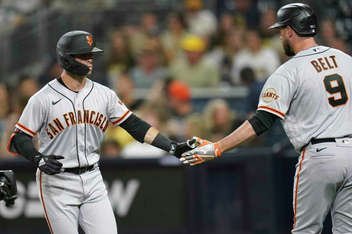 San Francisco Giants' Tommy La Stella, left, reacts with teammate Brandon Belt (9) after hitting a home run during the first inning of a baseball game against the San Diego Padres, Tuesday, Sept. 21, 2021, in San Diego. (AP Photo/Gregory Bull)