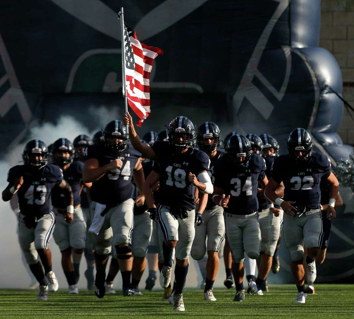 College Park wide receiver Holden Rook (19) holds an American flag as he leads the team onto the field before a high school football game at Woodforest Bank Stadium, Saturday, Sept. 18, 2021, in Shenandoah.