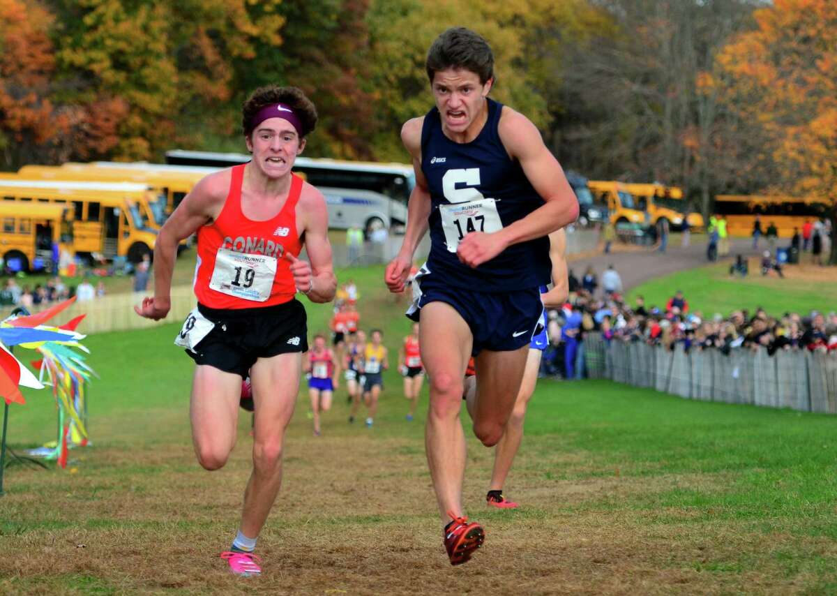 Staples' Morgan Fierro, center, stays ahead of Conrad's Callum Sherry to cross the finish line for third place during Class LL cross country championship action in Manchester, Conn., on Saturday Oct. 26, 2019.