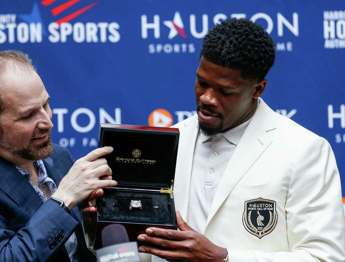 Former Houston Texans wide receiver Andre Johnson, center, was presented with his ring after being inducted into the Houston Sports Hall of Fame at the GreenStreet Promenade on Tuesday, Sept. 21, 2021, in Houston.