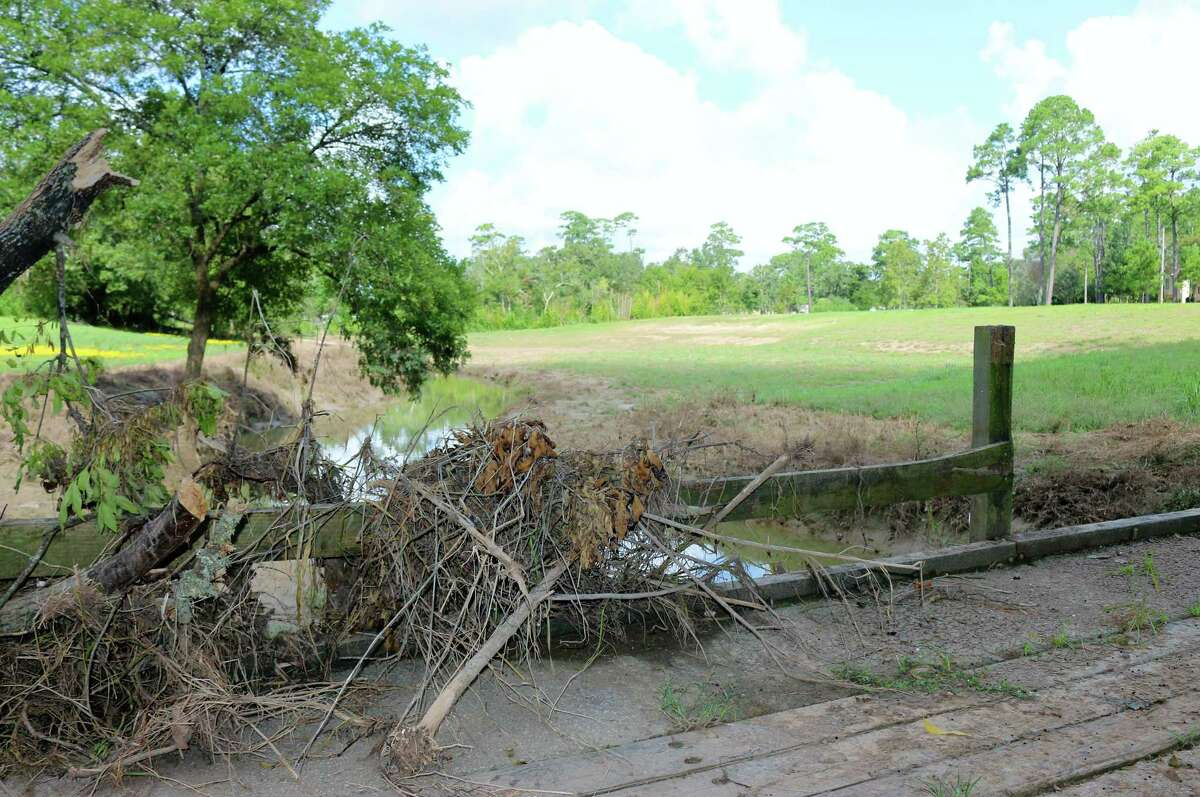 An abandoned bridge in the Imperial Estates subdivision is strewn with debris marking a recent high-water mark. The area beyond the bridge shows where the bank was cut back to create a detention area.
