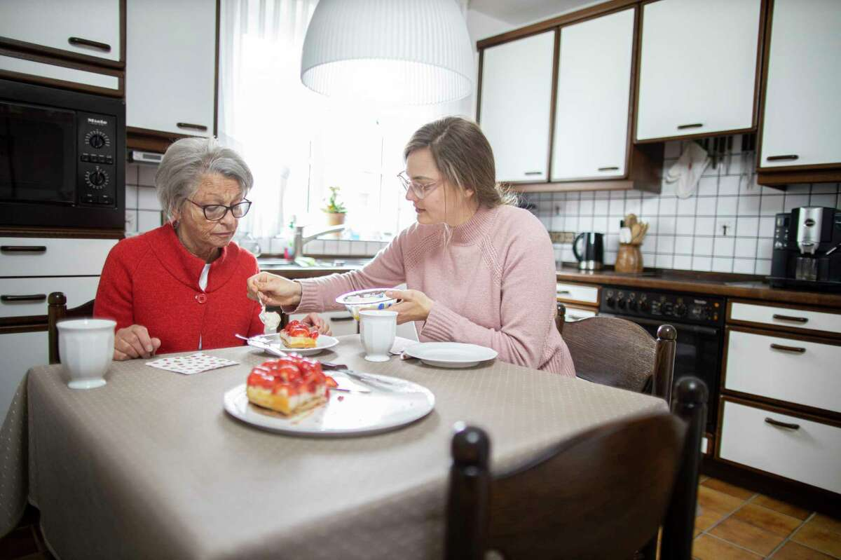 Two women eata meal together in Radevormwald, Germany.Spend a mealtimewith a loved one is a good way tonote how much food they eat or if they are eating well-balanced meals.(Photo by Ute Grabowsky/Photothek via Getty Images)