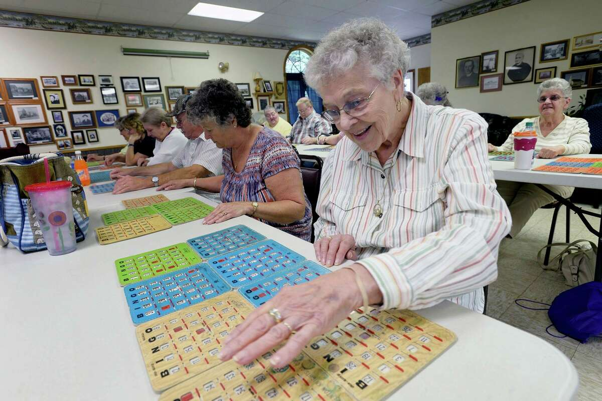 A 91-year-old resident looks over her cards during a game of Bingo atasenior center in Portland, Maine. (Photo by Shawn Patrick Ouellette/Portland Press Herald via Getty Images)
