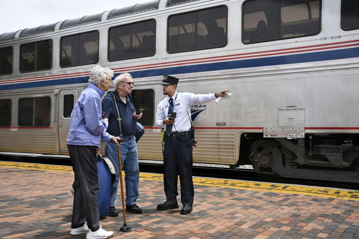An Amtrak conductor helps a senior couple board a train at the train depot in Lamy, New Mexico, near Santa Fe. (Photo by Robert Alexander/Getty Images)