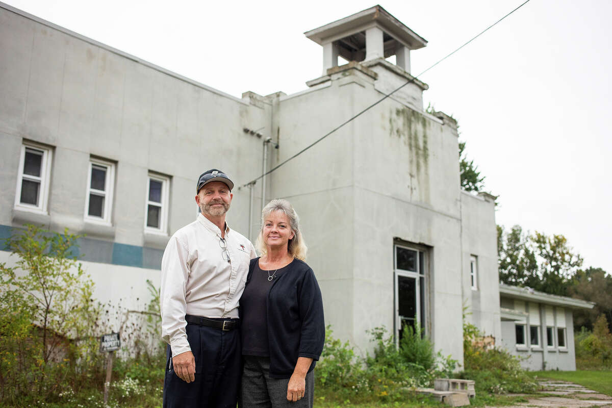 Greg and Lori Miiler pose for a portrait Tuesday, Sept. 21, 2021 in front of the dilapidated former Crane School at the corner of Gordonville and Badour Roads, where the townships of Ingersoll, Homer, Midland Charter, and Mt. Haley meet. The building has been purchased the Miilers, who plan to tear down the original school building and open up a business in the newer addition. (Katy Kildee/kkildee@mdn.net)