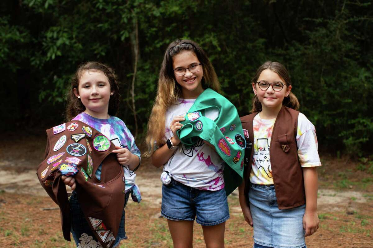 Girl Scout Troop 118037 members Emmie Likeness, 9, Amita Ramcharan, 10, and Rachel Rajabi, 8, pose with their vests to show off the Okay to Say mental health badge they earned late last year.