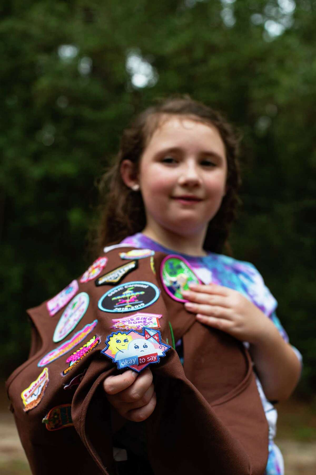 Girl Scout Troop 118037 member Emily Likeness, 9, shows her Okay to Say mental health badge, Wednesday, Sept. 1, 2021, in Atascocita.